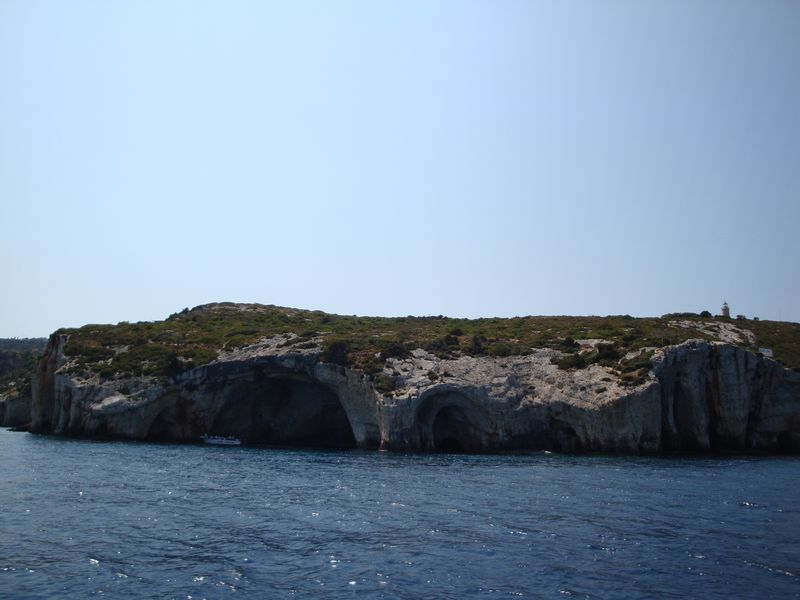 55. Голубые пещеры (Γαλάζιες Σπηλιές) - Фотографии с экскурсии вокруг острова, виды северной части. Вода неимоверно голубая! На известняках по уровню линии воды везде ярко-сиреневая полоса из-за кораллов. Здесь плавают очень интересные медузы - ярко оранжевые, пупырчатые, с торчащими черными волосками!!! На скалах гнездятся кармараны (птицы на подобие альбатросов), которые очень любят рыбу, и даже считается, что кармараны своим пометом могу вызывать пожары! Пещеры образуют арки и своды, через которые можно проплыть. Вода здесь несколько холоднее, чем на пляжах южной части!